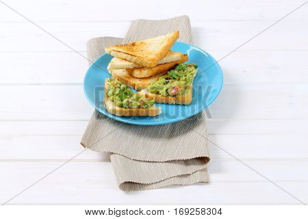 plate of toast bread with guacamole on beige place mat