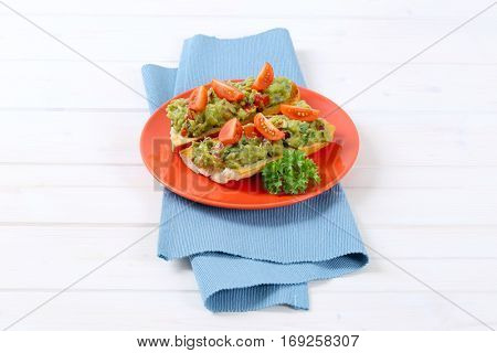 fresh baguettes with guacamole and tomatoes on red plate