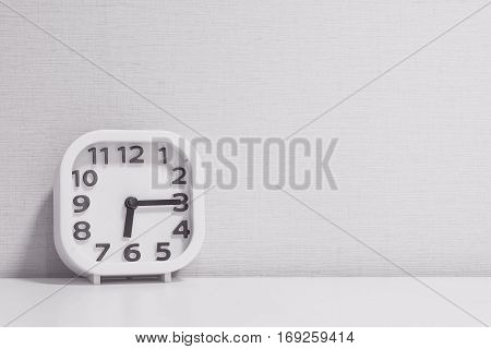 Closeup white clock for decorate show a quarter past six or 6:15 a.m. on white wood desk and cream wallpaper textured background in black and white tone with copy space
