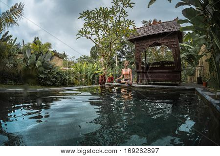 Young woman meditates in the tropical garden by the pool