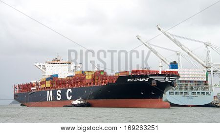 Oakland CA - January 20 2017: Multiple tugboats assist cargo ship MSC CHANNE to maneuver into the Port of Oakland.