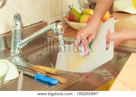 Household. Closeup woman doing the washing up in kitchen cleaning plastic cutting board