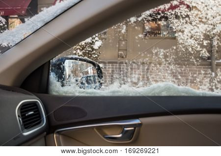Winter view from side window of car covered with droplets and snowfakes