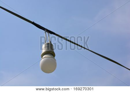 Power cord with lamp on blue sky background