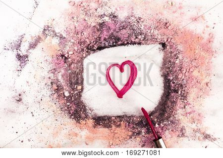 Lip gloss on white marble background, with traces of powder and blush forming a frame with a heart in it. 'Love Makeup' valentine card design