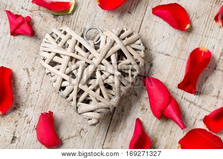 Closeup Of Heart-shaped Wicker Decoration And Rose Petals