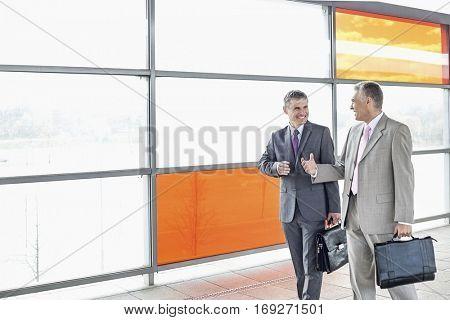 Happy businessmen talking while walking in railroad station