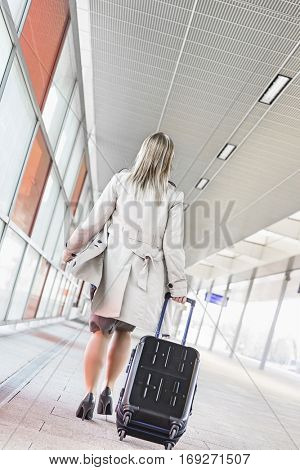 Full length rear view of young businesswoman with luggage walking in railroad station