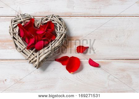 Overhead Of Wicker Rattan Heart Filled With Rose Petals