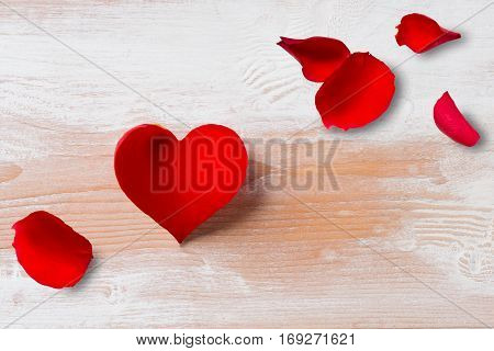 Rose Petals And A Heart-shaped Red Petal On Wooden Background