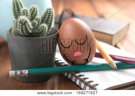 Egg With Sleeping Face On Work Desk Relaxing And Sleep From Hard Working Concept.