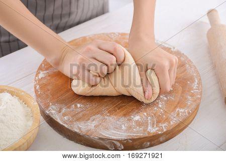 Woman kneading dough on kitchen table, closeup