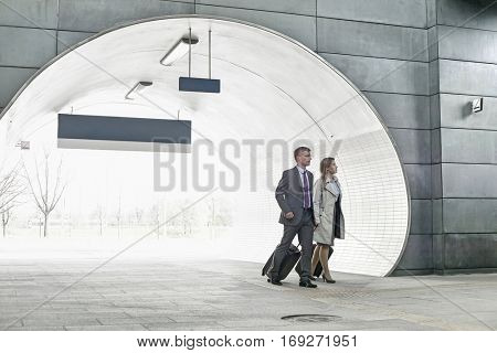 Businessman and businesswoman entering railroad station