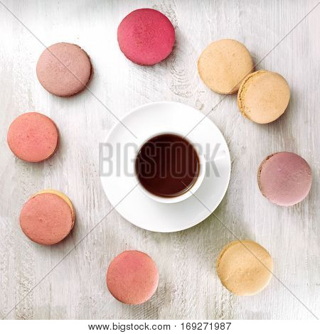 A square photo of a cup of coffee with various pastel coloured macarons around it, slightly toned
