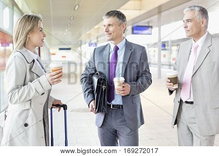 Businesspeople with coffee cups talking at railroad platform