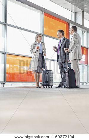 Full length of businesspeople talking on railroad platform