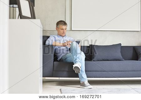 Full-length of Middle-aged man using digital tablet on sofa