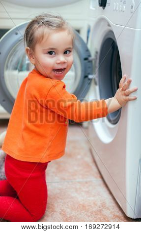 Child girl is looking into the washing machine