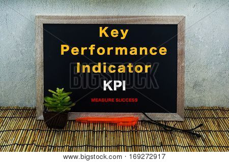 Business & creative concept,Key Performance Indicator KPI,Measure Success word on blackboard with green plant,pen & spectacle eyeglasses.