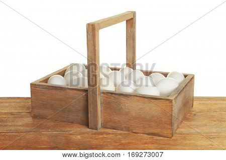 Raw eggs in wooden box on white background