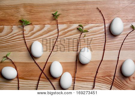 Composition of eggs and tree branches on wooden background