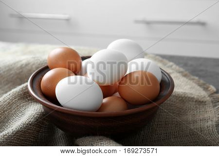 Bowl with raw eggs on kitchen table
