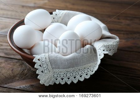 Bowl with raw eggs on wooden background