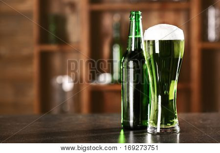 St. Patrick Day concept. Glass of green beer and bottle on bar counter