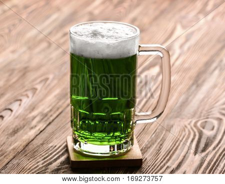 St. Patrick Day concept. Glass of green beer on wooden background