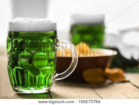 St. Patrick Day concept. Glass of green beer and plate with crisps on wooden table