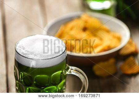 St. Patrick Day concept. Glass of green beer and plate with crisps on wooden table, closeup
