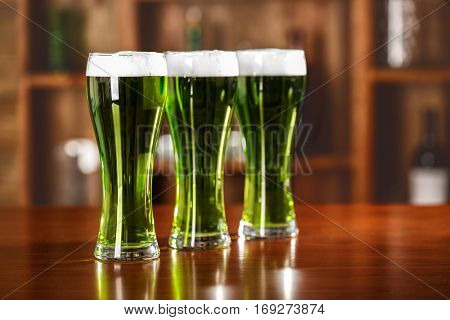 St. Patrick Day concept. Glasses of green beer on bar counter