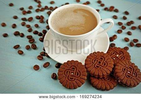 Cup of fresh coffee with cookies and beans on light blue background