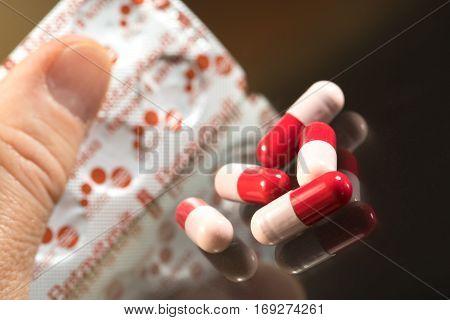 Man takes antibiotics capsule from the set