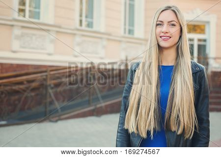 Beautiful young woman walking along street on autumn day