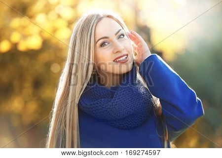 Beautiful young woman in autumn park on sunny day