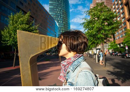 Girl standing in the center of the city and looking throw binoculars. Female tourist traveling in Germany, Berlin and overlooking city