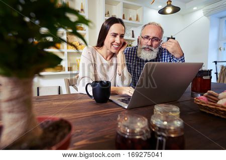 Low angle of content couple using laptop and leaning on the table while having tea in the kitchen. Tea with homemade cookies. Cookies and bagels in the box, wooden table. Rack focus on plant and