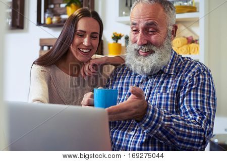 Close-up of astonished couple emotionally gesturing while looking at the screen of the laptop. Leased woman working with her colleague at home. Home kitchen interior