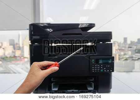 service engineer hold screwdriver for repair printer