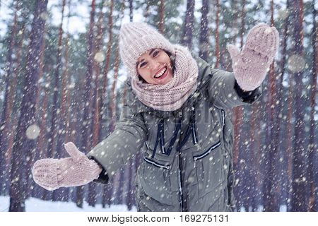 Low angle of Caucasian woman showing mittens at the camera in the wintry forest. Winter forest with trees full of snow. Elated woman in trendy winter clothes