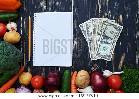 Top view of blank notebook with pencil, some of money enclosed with a set of vegetables over flat layout. Purchase list. Healthy food and healthy lifestyle concept. Currency. Dollars