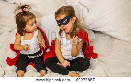 two little girls play costumes super-hero sitting on a white bedthe concept of leadershipvictory