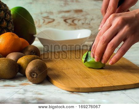 Woman cutting fruits on chopping board. Female hands cutting kiwi fruits close up.
