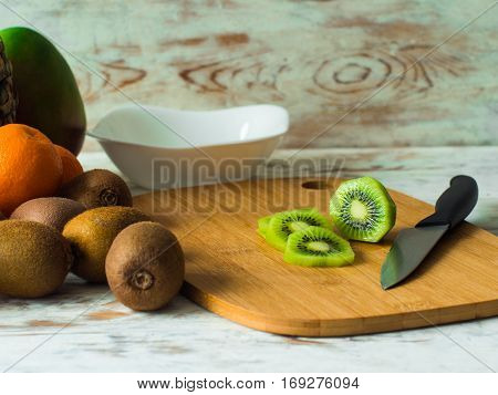Still fruits on the table. Kiwi with knife on chopping board