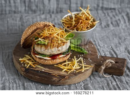 Grilled chicken and fries burger on wooden cutting board