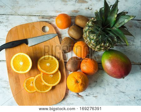 Top view of fruits on the table. Oranges, kiwi, mango, pinnaple. Healthy food and diet concept on vintage boards.