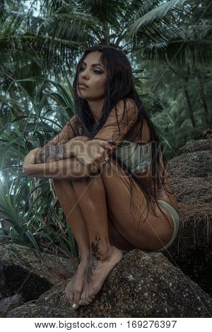 Sensual young brunette beauty wearing mint underwear with wet hair sitting on the rock over tropical green jungle background