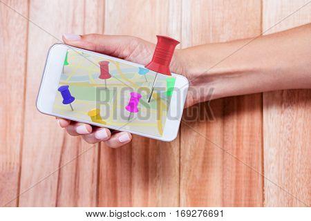 Close-up of red thumbtack against feminine hand holding smartphone