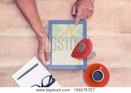 Close-up of navigation pointer against overhead view of person holding on digital tablet